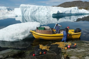 Inuit fishermen prepare a net as ice floats behind them at the mouth of Ilulissat Icefjord last summer