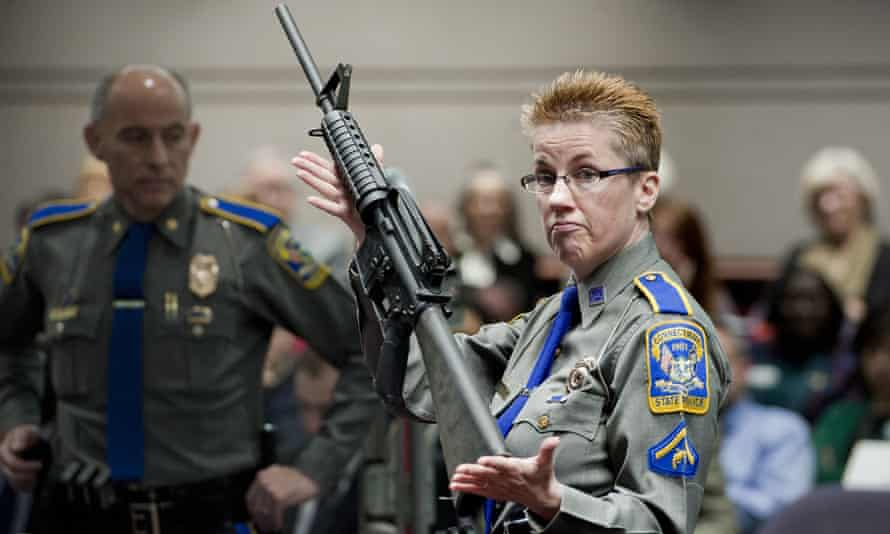 A Connecticut state police officer holds up an AR-15 rifle during a state legislative hearing on gun laws.