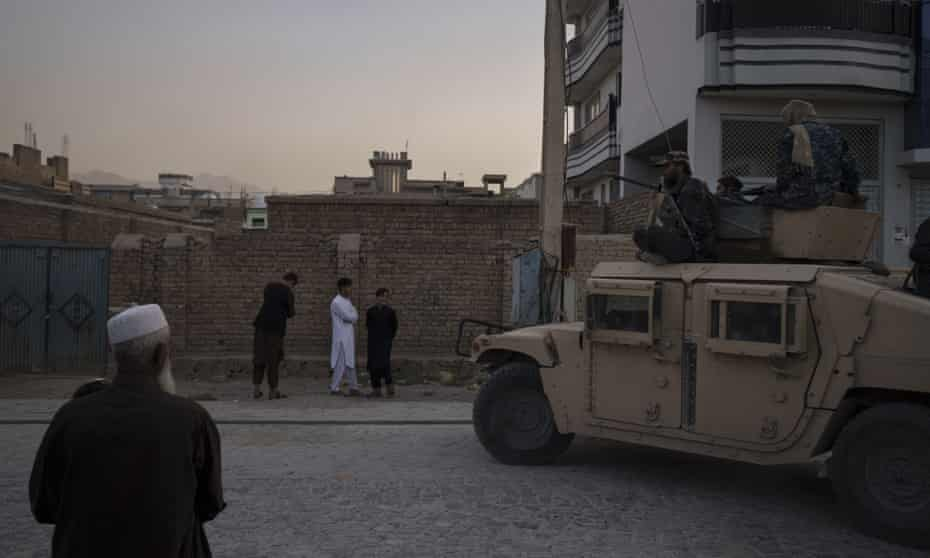 Afghans watch as Taliban fighters ride atop a Humvee