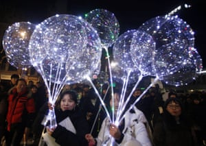 People hold balloons during celebrations in Seoul, South Korea