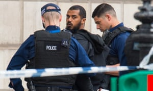 Armed police detain a man