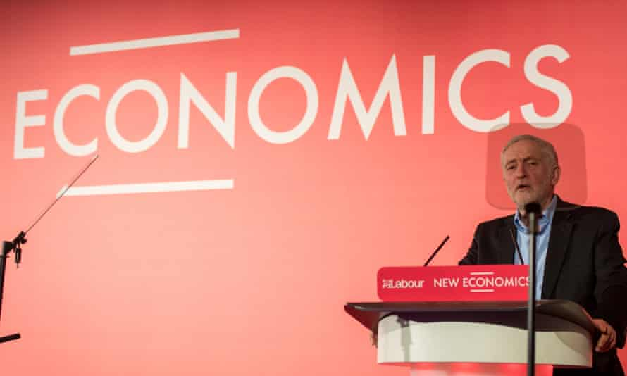 Jeremy Corbyn at a conference, with Economics behind hom.