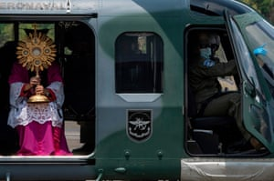 Panama City, Panama Archbishop José Domingo Ulloa holds the Blessed Sacrament as he sits on a helicopter. He will be flown over the capital and surrounding areas to 'protect the country from disease'