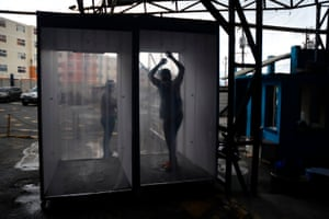 A worker is sprayed with disinfectant as he arrives for his shift at KP Textil.