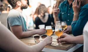 Glasses of beer on a table surrounded by outdoor drinkers at Brussels Beer Project in Brussels, Belgium.