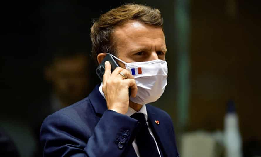 French president Emmanuel Macron speaks on his mobile phone during a round table meeting at an EU summit in Brussels.