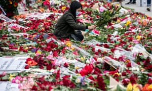 A protester lays down flowers in front of the Hall of Justice in Los Angeles, part of the 'Rose From Concrete' action inspired by a poem by late rapper Tupac Shakur, while hundreds continue demonstrating over the arrest and death in police custody of George Floyd.