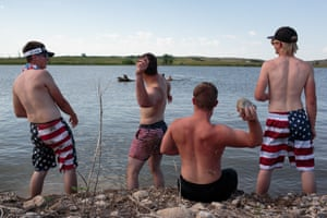 """Youth of Watford City and Fort Berthold Reservation North DakotaJamison, Jade, Gregory and Nick, throw rocks at their friends swimming in the distance, celebrating the 4th of July holiday on the Fort Berthold Reservation, 3 July 2017, North Dakota. The group is saying goodbye to one of their friends, Logan, who leaves in two days for boot camp for the Marines. His grandpa inspired him, and he didn't want to work on the oil elds.Jamison, Jade, Gregory, and Nick throw rocks at their friend, Logan, swimming in the distance. Later in the evening, the boys will celebrate the 4th of July under the lights of a casino, parked in a gas station, watching the reworks explode over Fort Berthold Reservation in North Dakota. """"Are you sure about this?""""""""No, but I'm going,"""" says Logan. He ships o to California for the Marine boot camps in five days. He didn't want to work in the oil fields, or live on the reservation, or on its border town. Fort Berthold Reservation, North Dakota."""
