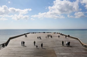 Hastings residents walk on the town's newly reopened pier