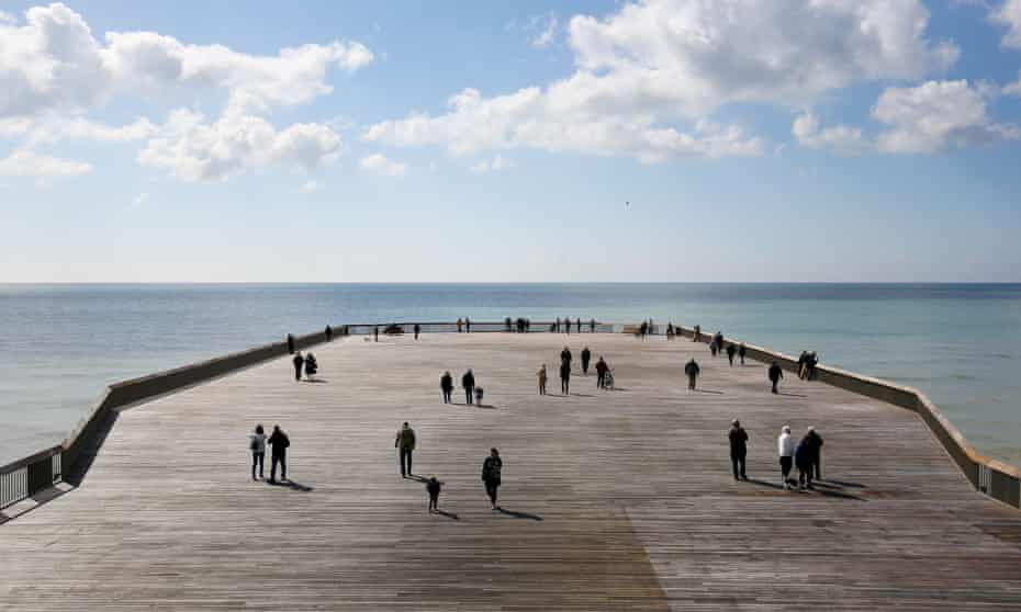Walking 'the Plank': the reimagined, clutter-free Hastings Pier. Below: the i360 in Brighton, opening next month, forms a 'vertical pier'.