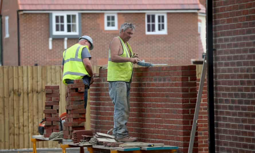 Construction workers build new houses on a housing development in Middlewich, England