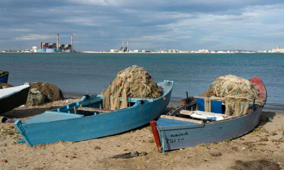 Fishing boats and nets at Port de Rades, and behind, polluting industry at la Goulette
