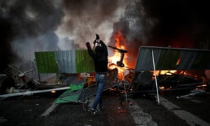 A protester throws a scooter onto a burning barricade in Paris