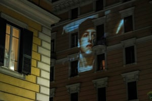 Rome, Italy. A feature film is projected on the facade of a building to entertain confined residents