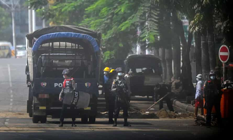 Police stand guard on a road in Yangon on Friday as security forces continue to crack down on protests against the Myanmar coup.