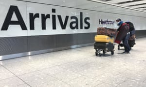 A passenger wears a mask as he arrives at Heathrow