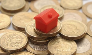 A red plastic house on top of a pile of pound coins