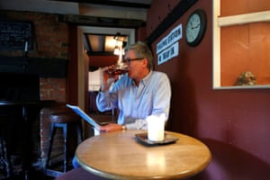 A man enjoys a pint inside the Fox and Hounds pub used as a polling station in Watlington in Oxfordshire.