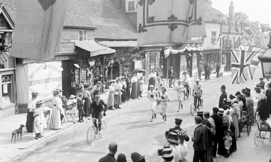 Black and white photograph showing street scene; three or four runners in white shorts and shirts are visible, accompanied by cyclists; the streets are lined with a sparse crowd of men and women in Edwardian dress, a baby in a carriage, and a couple of dogs.