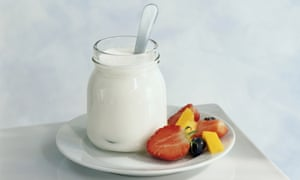 Jar of yoghurt and freshly cut fruit on plate, close-up