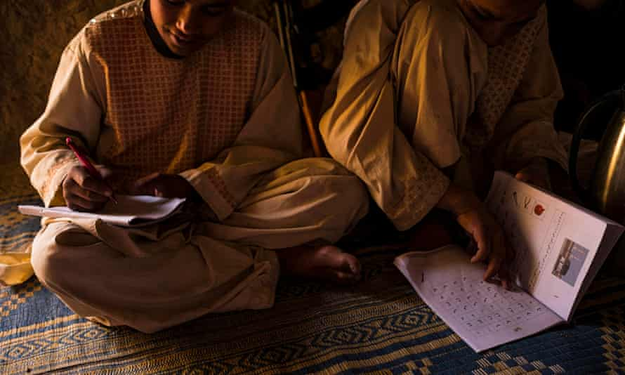 Habib* and Nabi* do their homework in the mud-walled compound the family shares