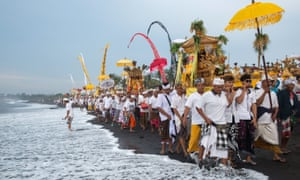 A procession heads down a beach in Bali for a melasti ceremony in the run-up to the Day of Silence.