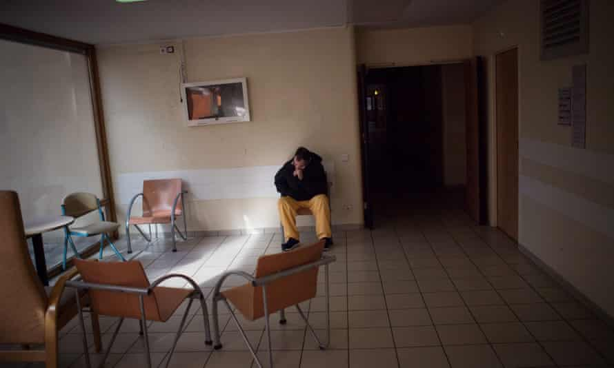 A patient in a psychiatric hospital sits in an empty waiting room