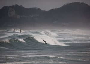 Surfers ride the waves at Tairatoyoma beach near the site of the Fukushima nuclear disaster