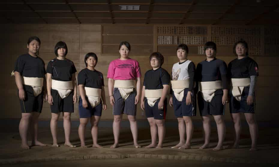 Eight of the current nine members of the Asahi University women sumo team pose for a group photo by the Dohyo
