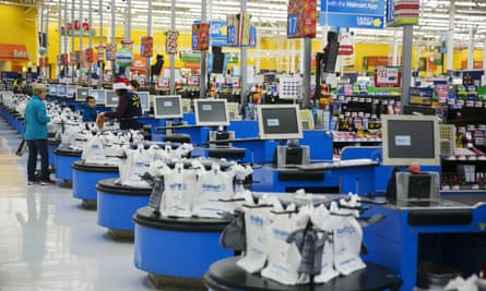 Employees work at the checkout counters of a Walmart store in