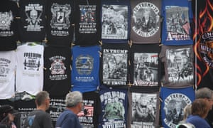 Passersby look at a wall of Trump T-shirts for sale at Laconia, New Hampshire's bike week.