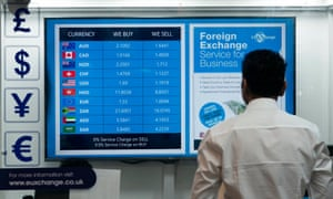 a man stares at a foreign exchange money board