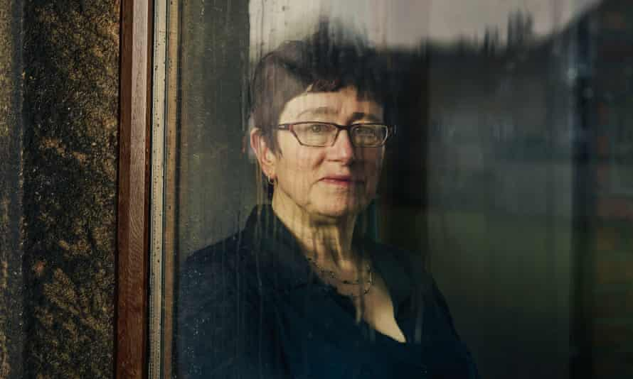 Linda Gask looking out of a rain-streaked window