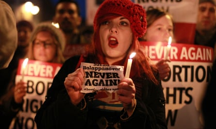 Demonstrators hold placards and candles in memory of Savita Halappanavar during a march in Dublin calling for legislative change on abortion, November 2012
