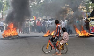 Indian children look on as activists burn tyres during a statewide strike in Bangalore in September 2016.