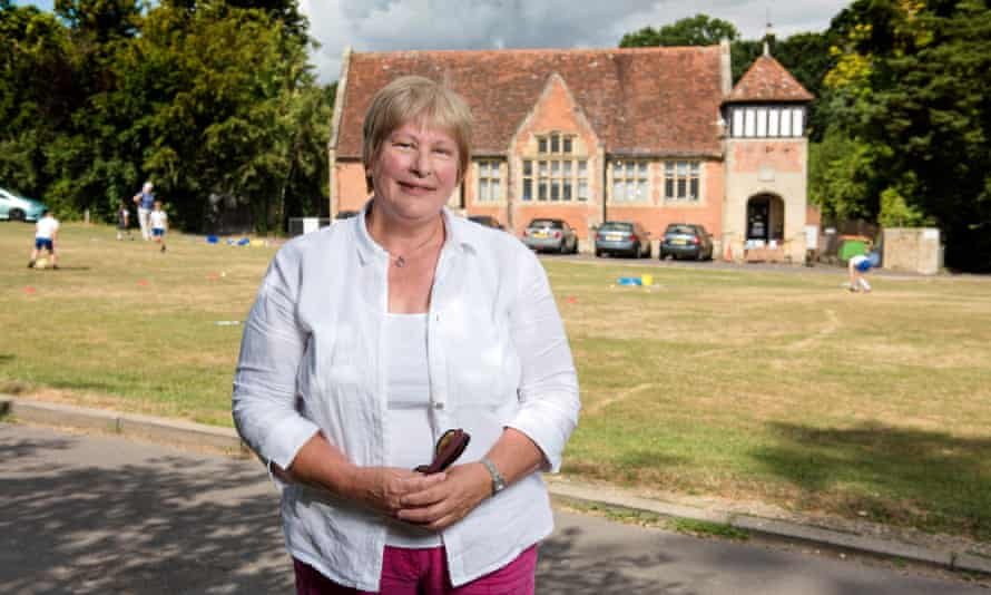 Headteacher in front of green and village school