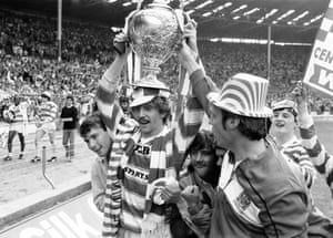 The man of the match, Brett Kenny of Wigan, holds the Challenge Cup aloft as he celebrates with fans.