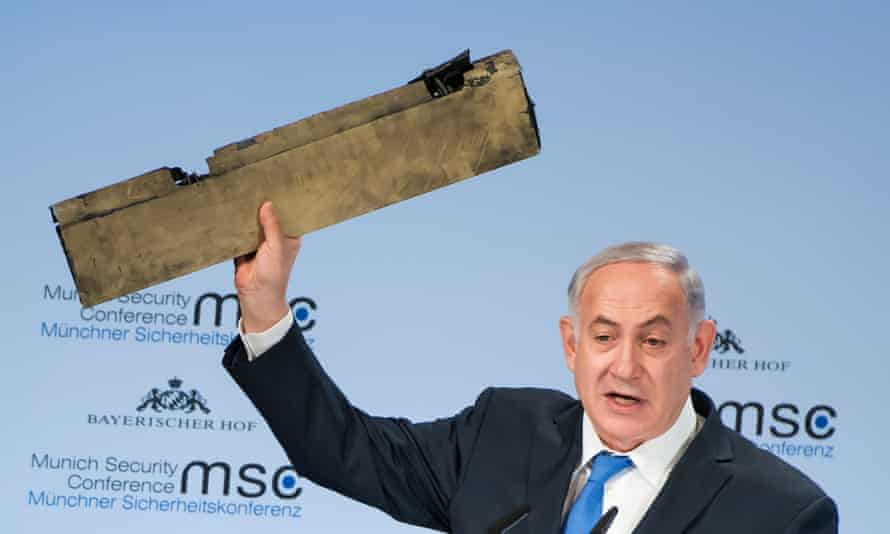 Israeli PM Benjamin Netanyahu holds up an object he claims is a piece of an Iranian drone shot down in Israeli airspace.