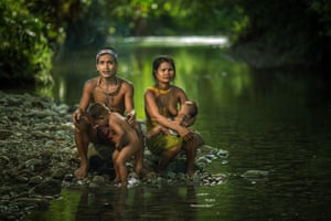 A young Mentawai family sit together on the side of the river