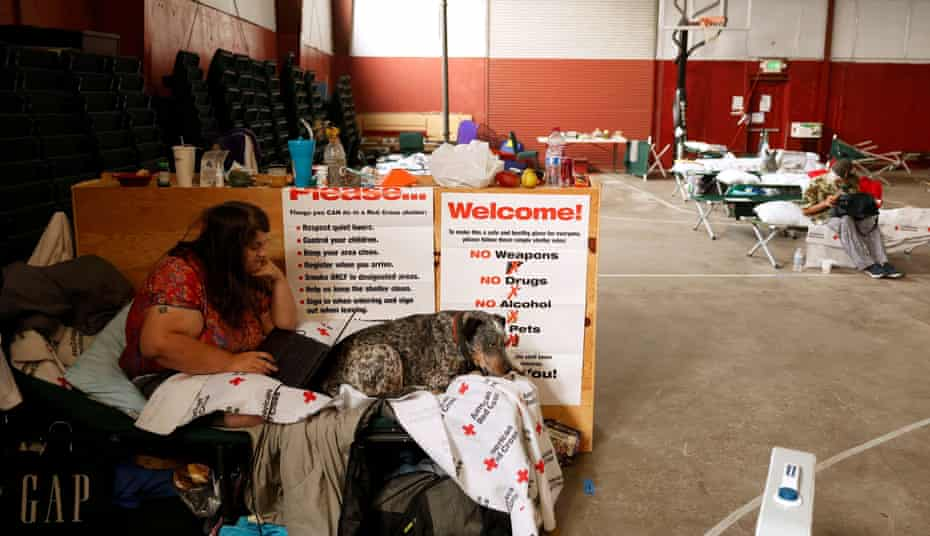 Jack Romero shares her cot with her dog Rascal at a Dixie fire evacuation center run by the Red Cross in Quincy.
