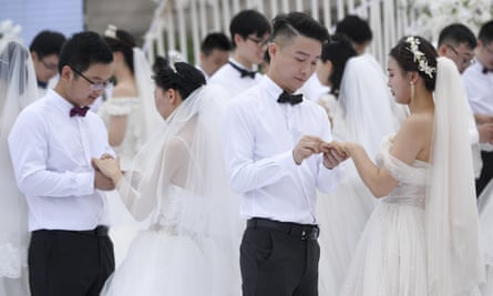 Newlywed couples attend a group wedding ceremony at Juzizhou Island Landscape in Changsha, Hunan Province of China in May 2020.