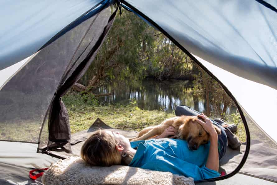 Alienor Le Gouvello lying in her tent with her dog Fox.