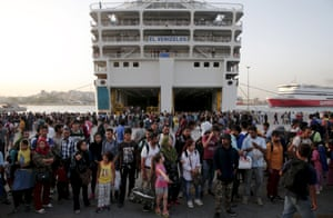 People wait to board a bus following their arrival onboard the Eleftherios Venizelos passenger ship at the port of Piraeus, near Athens.
