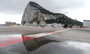 Pedestrians cross the asphalt at Gibraltar international airport in front of the Rock, near the border with Spain.
