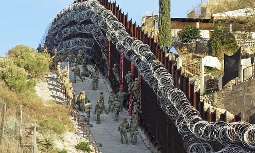 US army troops place additional concertina wire to the border fence on a hillside above Nelson Street in downtown Nogales in 2019.