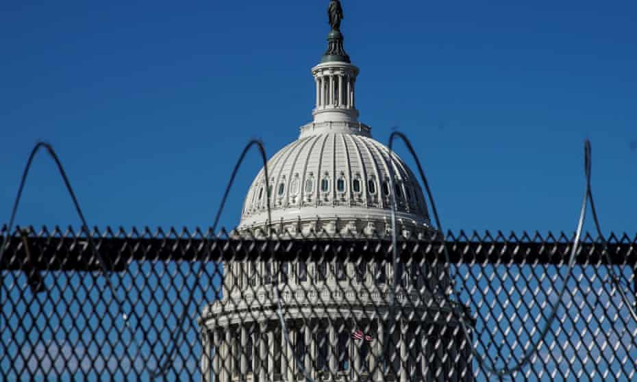 The Capitol building seen behind barbed wire fences.