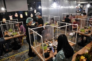 People eat in between plastic partitions, set up in an effort to contain any spread of the COVID-19 coronavirus, at the Penguin Eat Shabu hotpot restaurant in Bangkok on May 5, 2020.