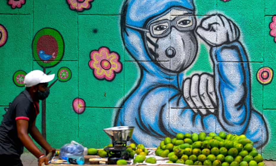 A fruit vendor pushes his cart past a Covid-inspired mural in Delhi. Some researchers say the Covid death toll in India could be as high as 4 million.