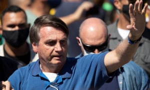Jair Bolsonaro greets supporters at a demonstration outside his presidential palace in May.