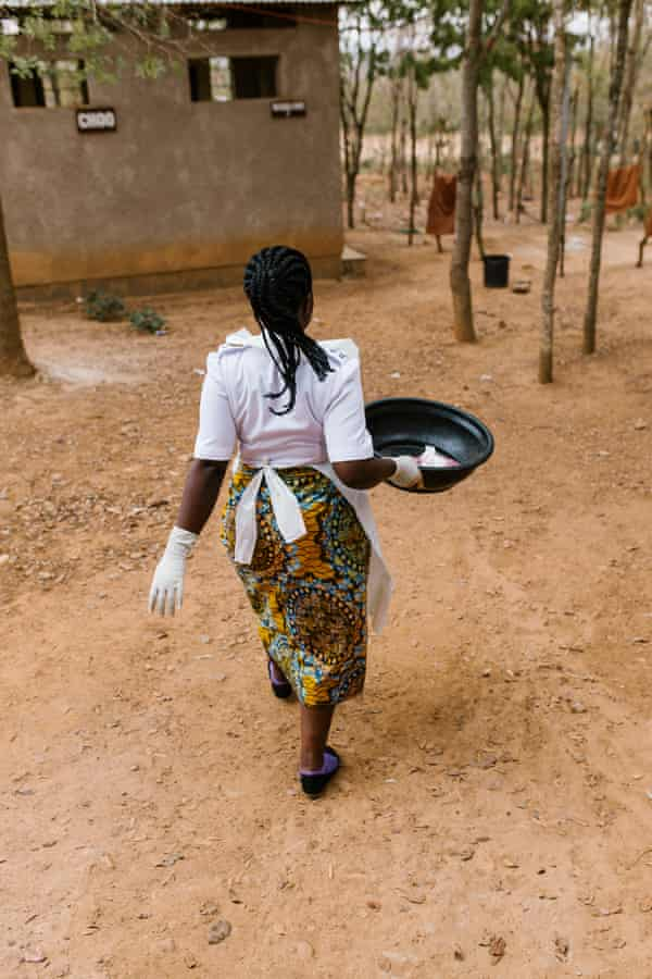 Nurse-midwife Jackeline Gideon Mwiguta carries the placenta and other waste out to the clinic's disposal pit
